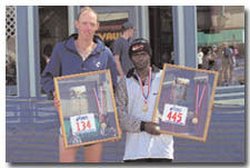 Ken Flint, No. 134, of Durango, and Jon Ndungu, No. 445, of Farmington, display their third and second place awards, respectively, Sunday at the post-marathon activities on Main.