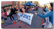 Lisa Mills, of Littleton, takes the honors of being the first woman to cross the marathon finish line with a time of 3:22