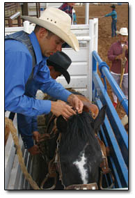 A Saddle Bronc rider prepares his horse prior to the competition sponsored by the Apaloosa Trading Co.