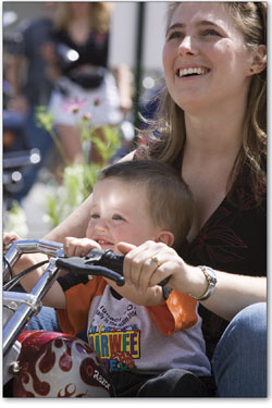 Keyton Cugnini, 2, works the handle bars of his mini-chopper as his mother, Tiffany, sits behind him.