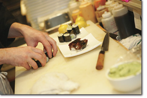 Jason Burgett, sushi bar manager, prepares a roll at East by Southwest Monday evening.