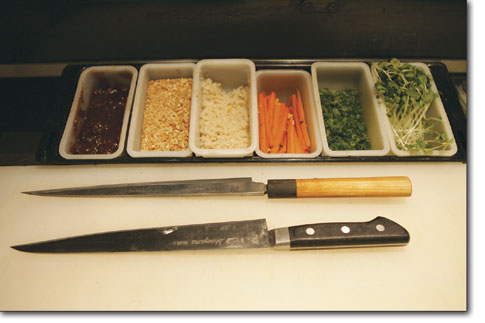 A pair of sushi knives and a collection of ingredients sit ready and waiting on the sushi bar at East by Southwest.
