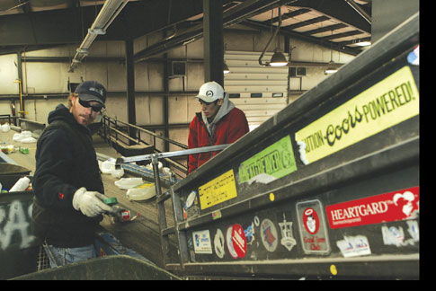 Aluminum cans are lifted up a conveyor belt before being crushed and stored as large blocks.