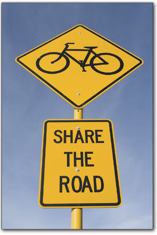 A pair of signs hang from a pole along Florida Road urging motorists and cyclists to play nice.