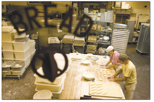 Bernard Castellain and Jeffe Morehart shape dough into what will soon be a small baguettes.