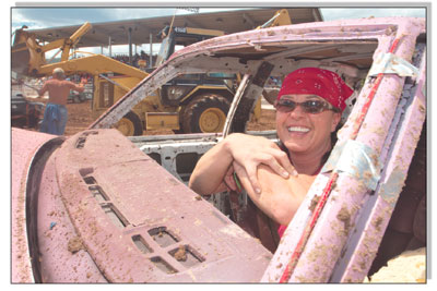 Krissi Elliot, from Cortez, gives a muddy smile as she waits to be towed out of the arena.