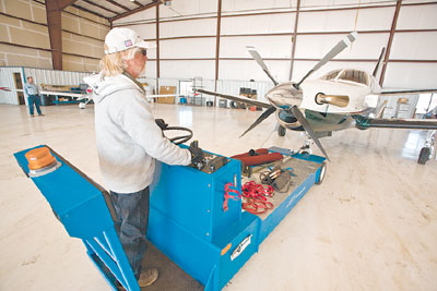 Jim Flory carefully pushes a plane back into the hangar for storage.