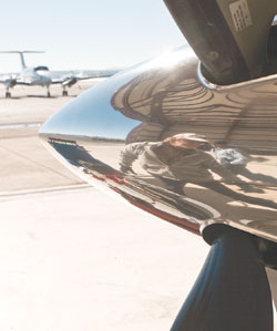 Jim Flory, reflected, pulls an aircraft from the hangar.