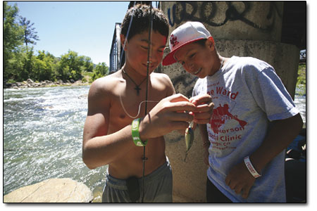 Kyle Duran (left) and Lawrence Mayberry tie on a lure under the train bridge.
